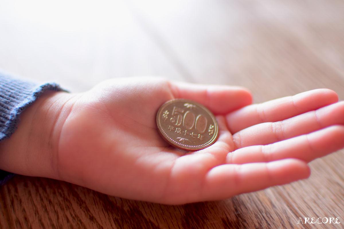 子供の手と500円玉